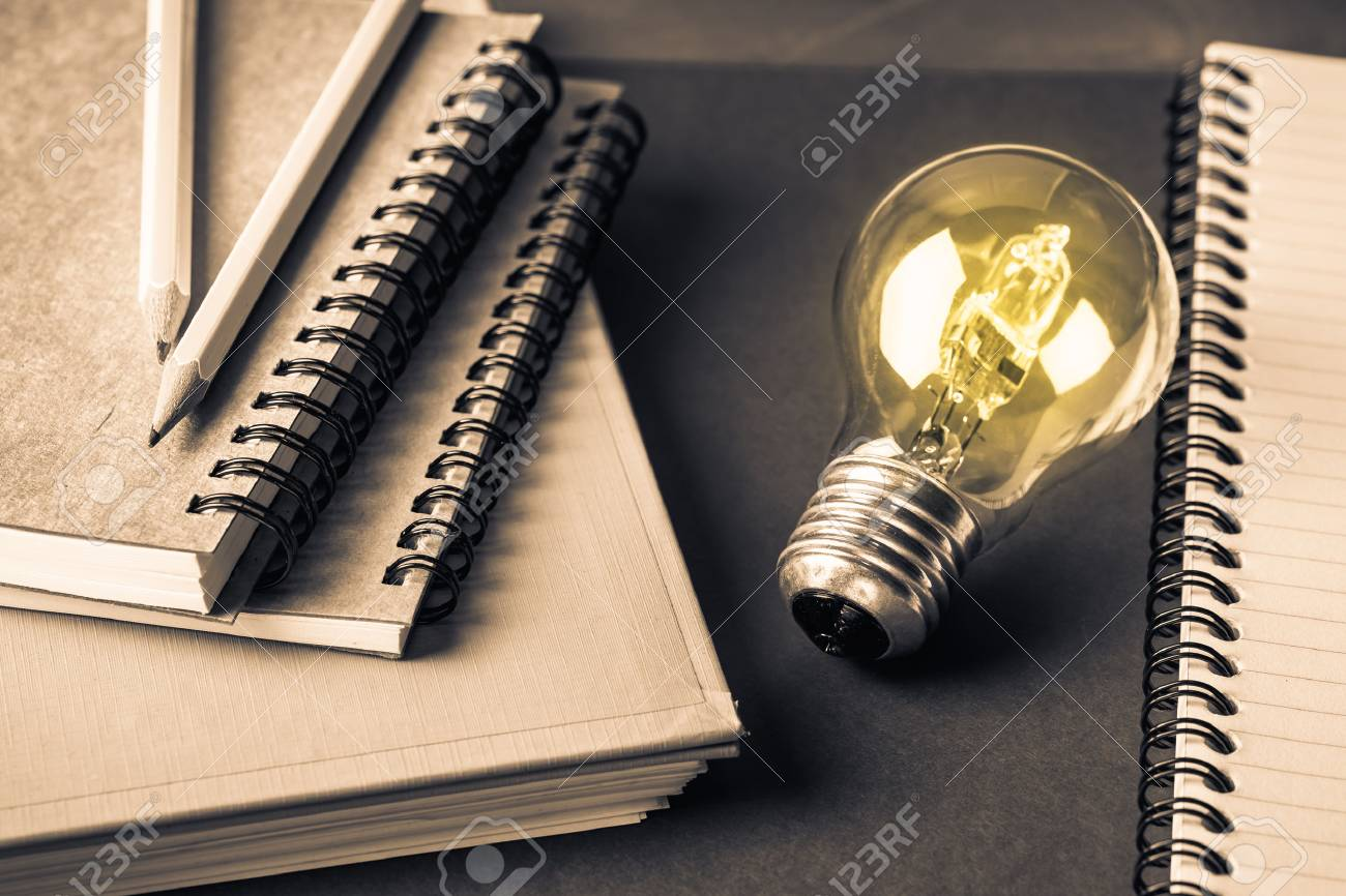 glowing light bulb with many notebooks for creative writing concept