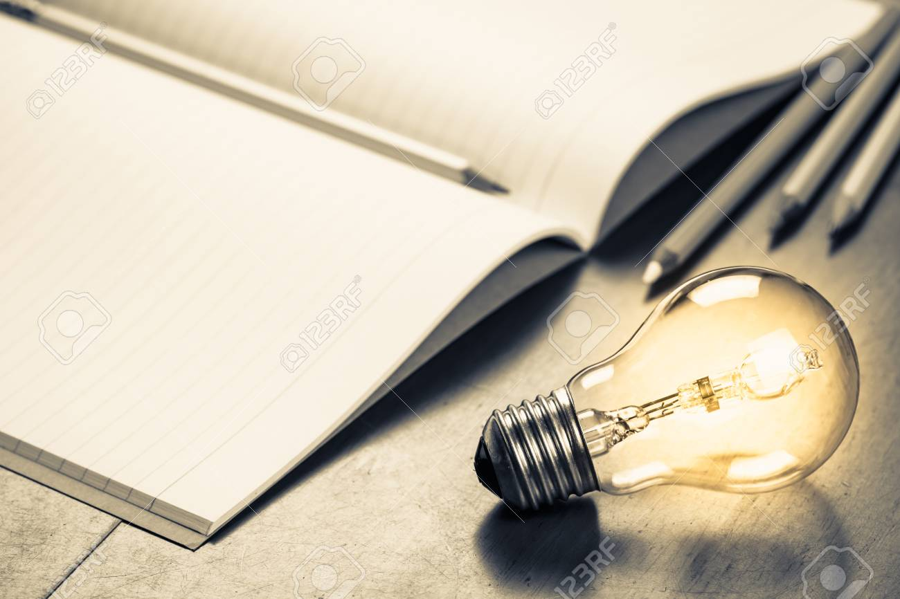 glowing light bulb with pencils and notebook, creative writing