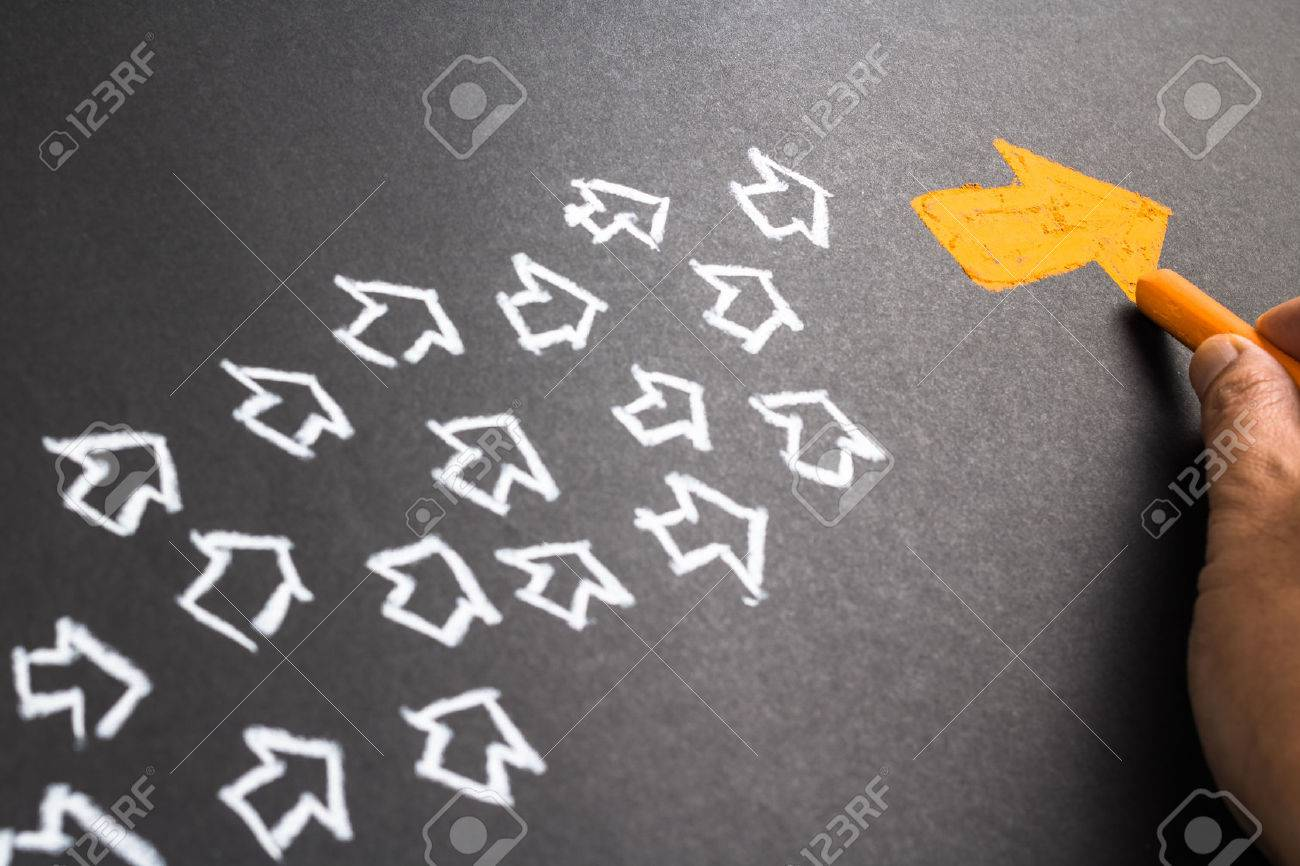 Hand drawing orange arrow as trend leader with many white arrows as follower - 50478287
