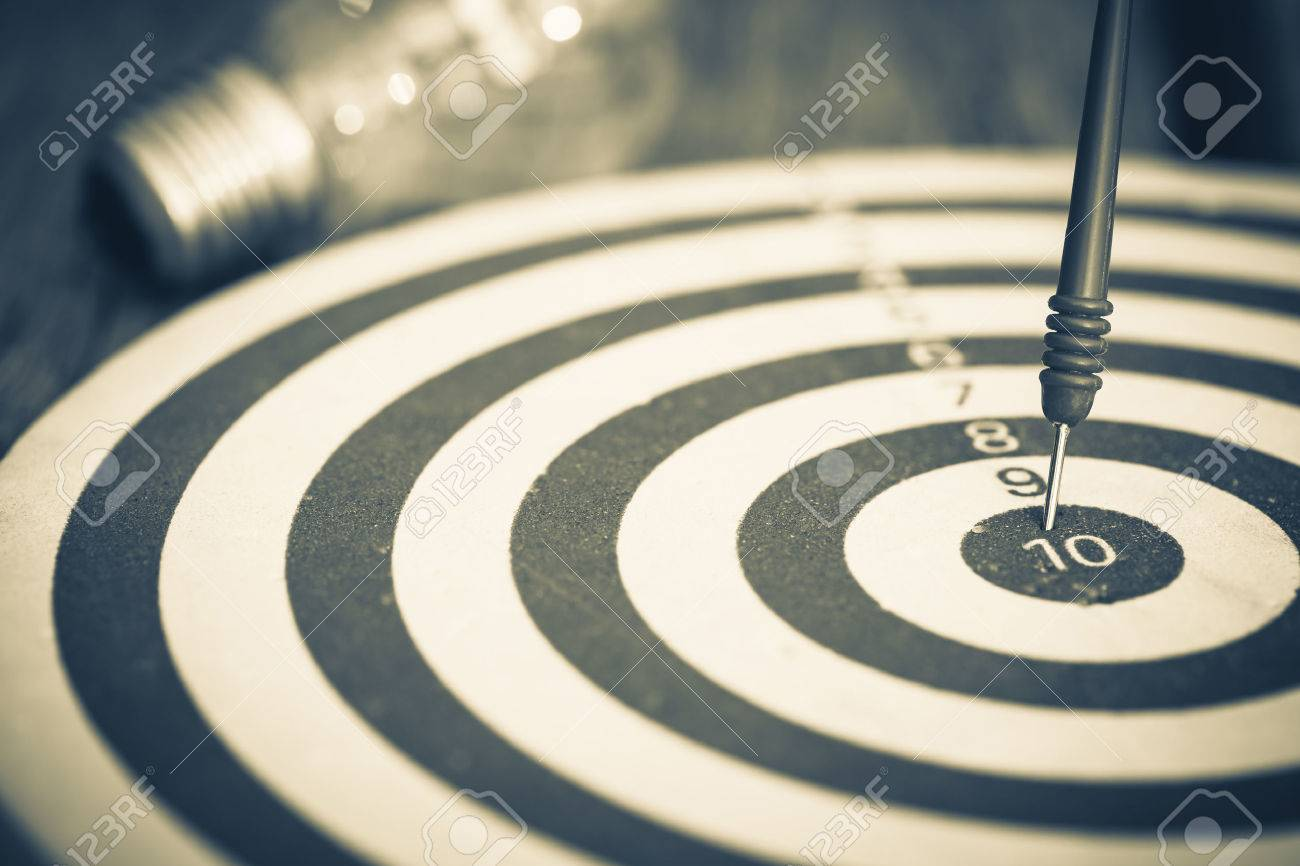 Smart goal setting, dart hit the center of dartboard with light bulb on background - 54764486