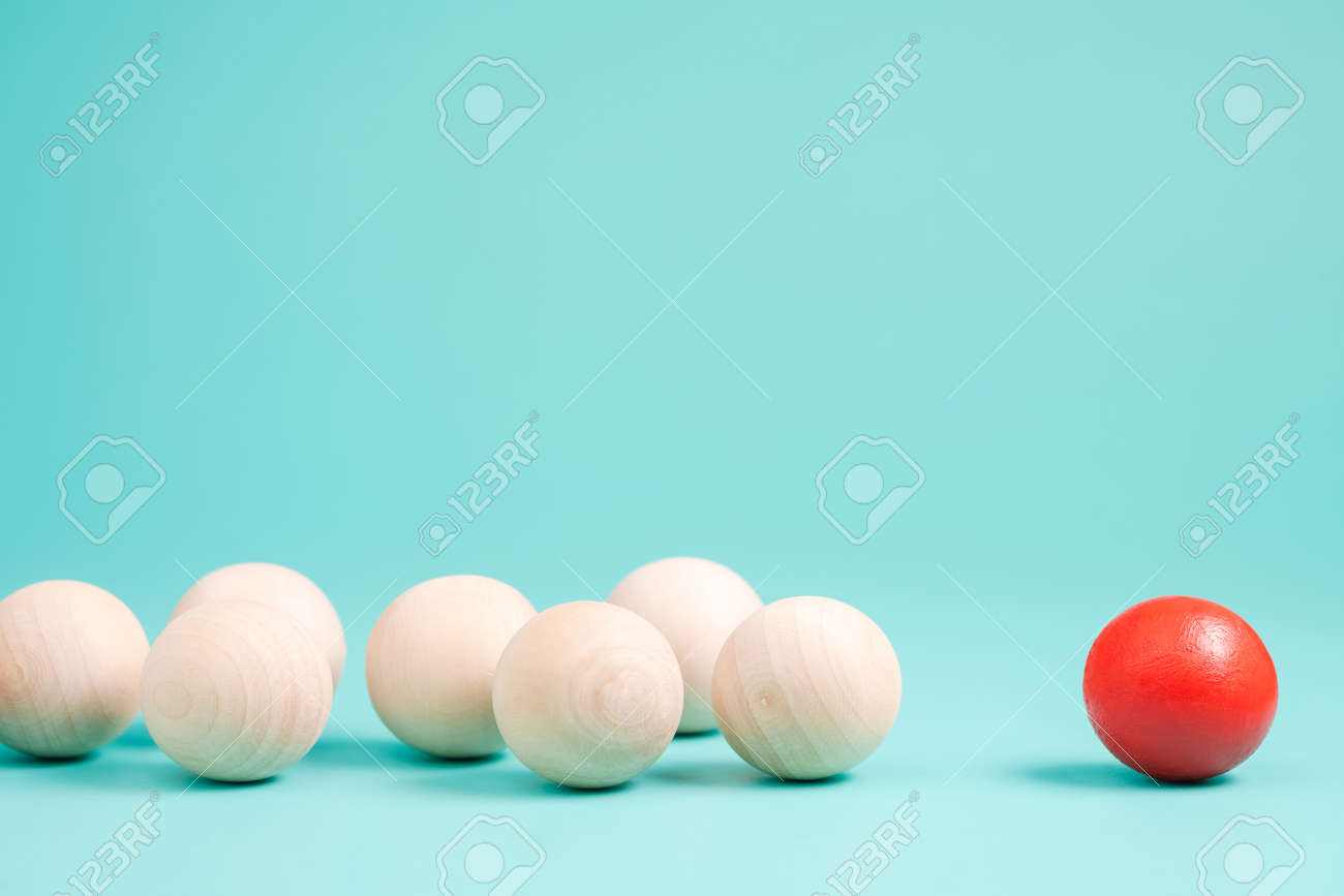 Different small red ball in the group of wooden balls on green background, leader or influencer with follower, branding and marketing concept - 166448101