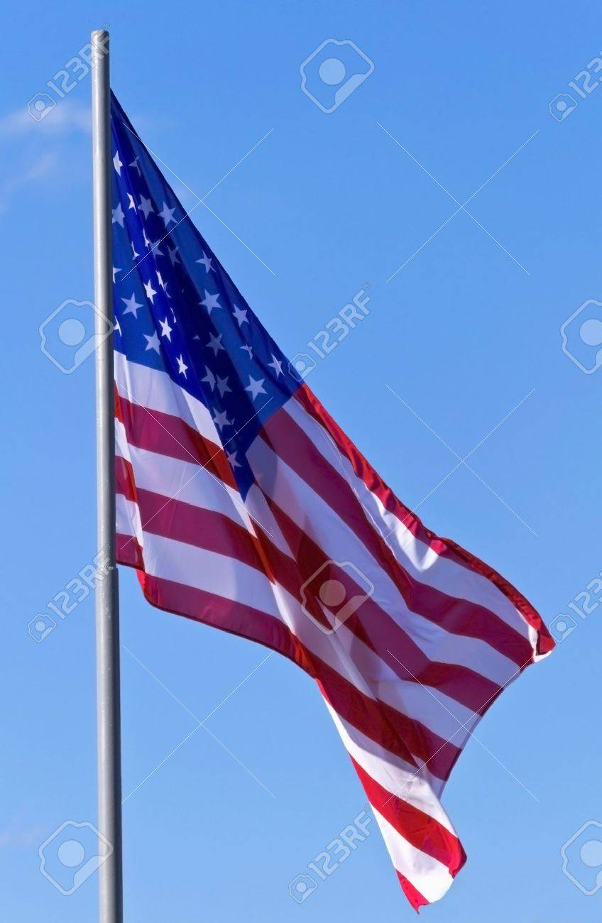 U S flag on a background of blue sky - 15561878