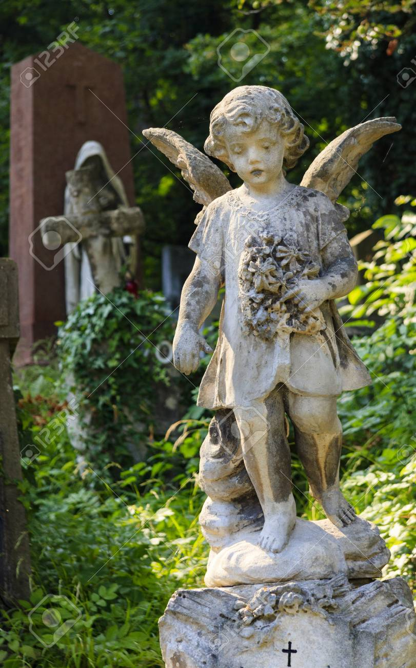 A statue of an angel in an old cemetery. - 84789920