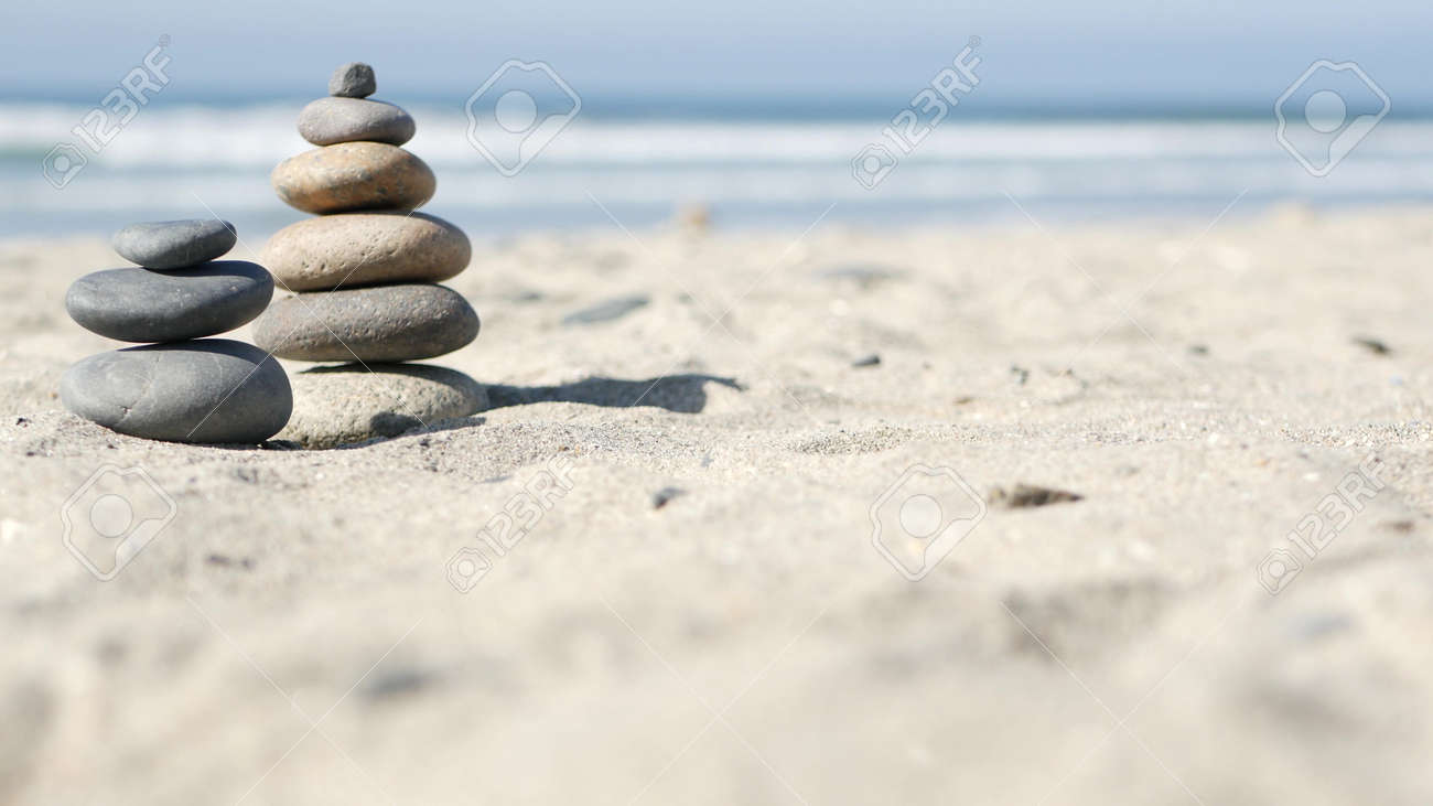Rock balancing on ocean beach, stones stacking by sea water waves. Pyramid of pebbles on sandy shore. Stable pile or heap in soft focus with bokeh, close up. Zen balance, minimalism, harmony and peace - 169279383