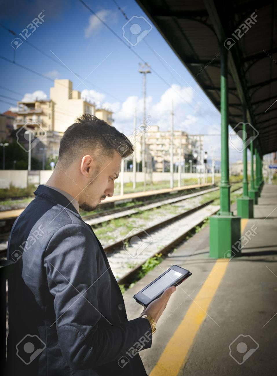 9de5f352ff Archivio Fotografico - Uomo che legge un tablet o ebook in una stazione  ferroviaria, mentre è in attesa per il trasporto pubblico