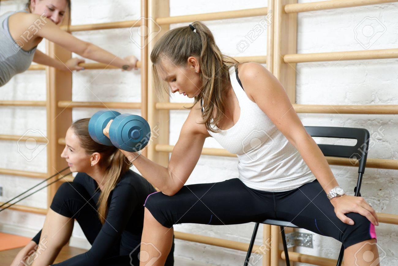 Banque d images - Jeune femme faisant biceps exercice boucle avec des  haltères dans une salle de sport c9a40558b46