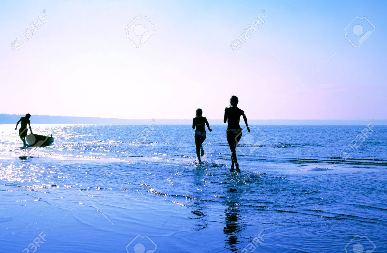 silhouette image of two running girls and muscular man in water Stock Photo - 849668