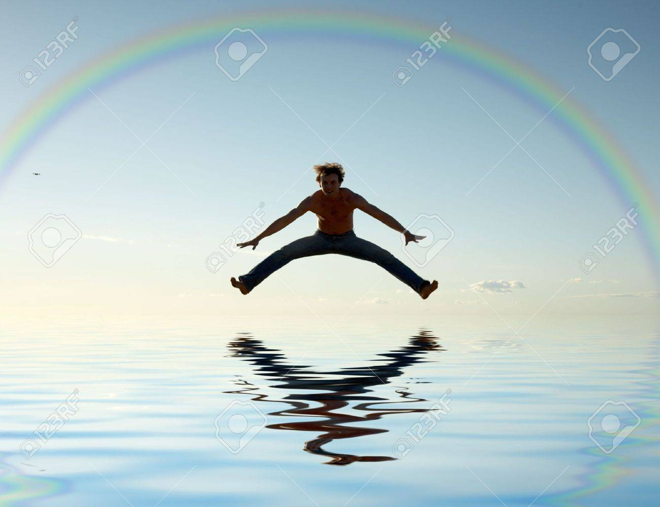 sporty man jumping under big colorful rainbow Stock Photo - 953067