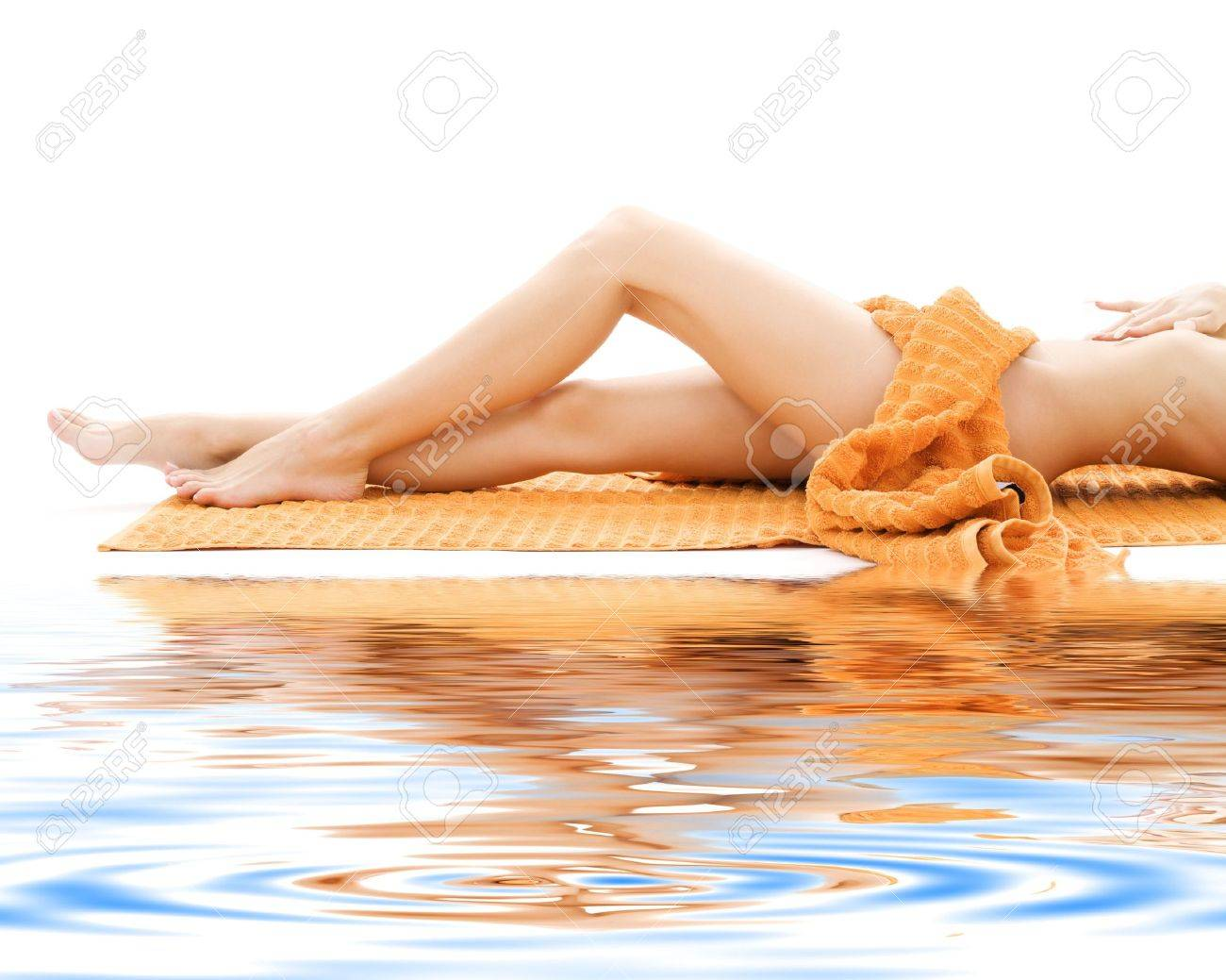long legs of relaxed lady with orange towel on white sand Stock Photo - 3465276