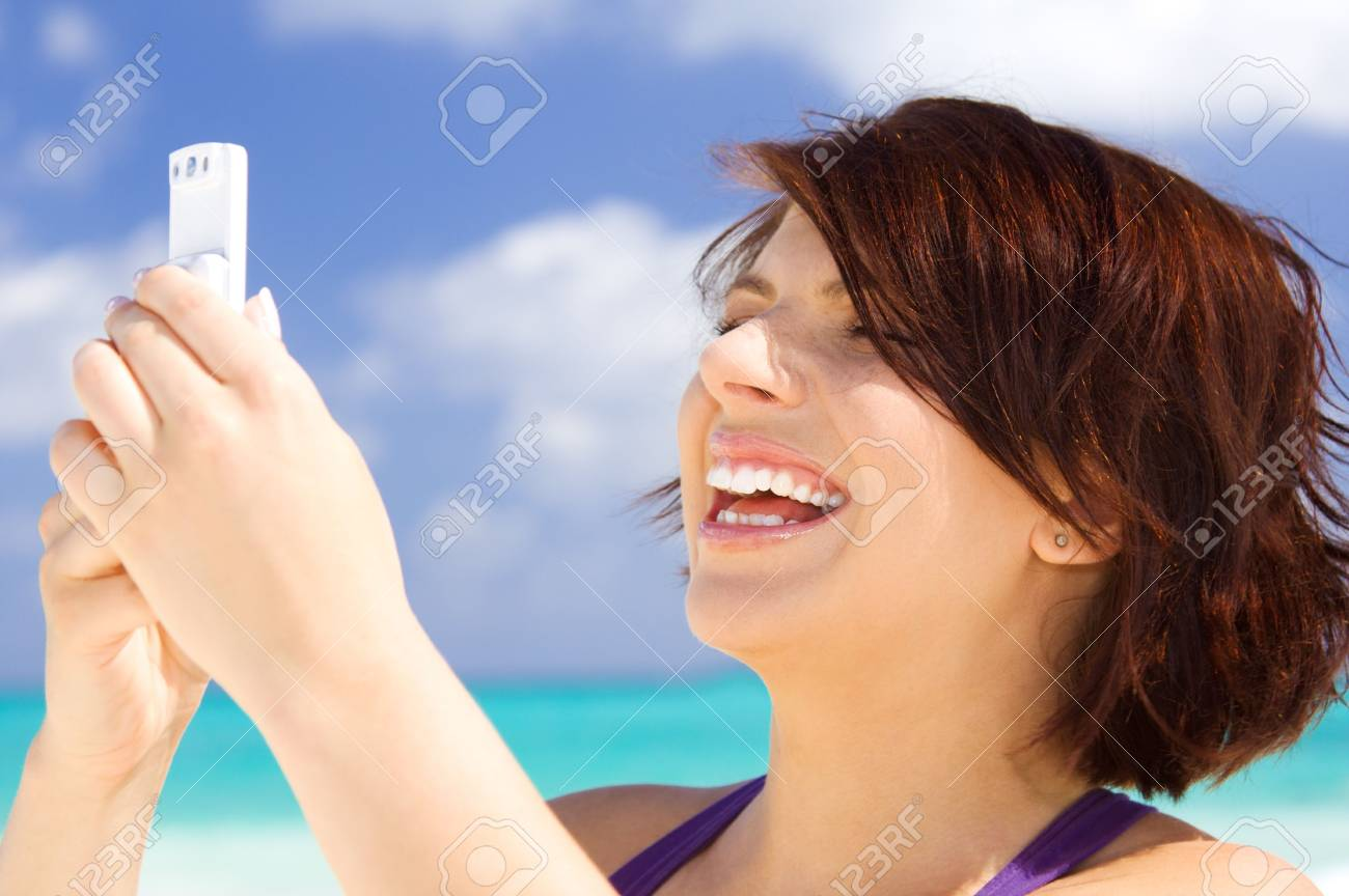 happy woman with white phone on the beach Stock Photo - 4211829