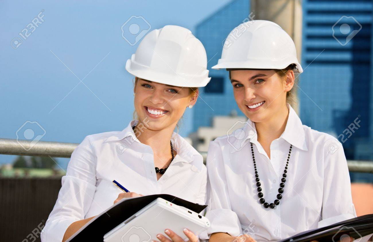 female contractors in a front of building site (focus on blonde) Stock Photo - 4562549