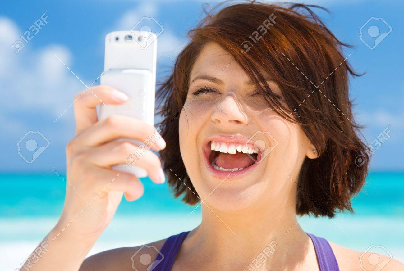 happy woman with white phone on the beach Stock Photo - 4780024