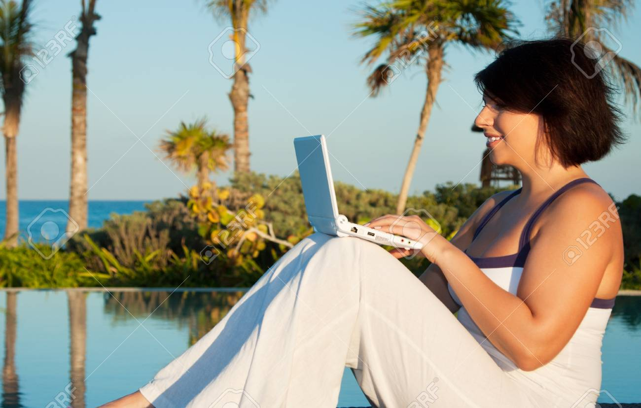 evening light picture of woman with laptop computer at tropical resort Stock Photo - 5348265