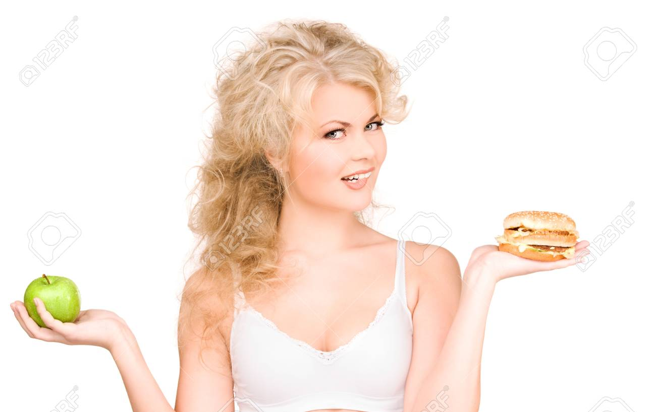 young beautiful woman choosing between burger and apple Stock Photo - 6663721