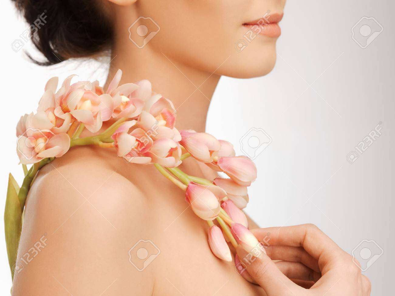closeup picture of woman s shoulder and hands holding orchid flower Stock Photo - 17601716