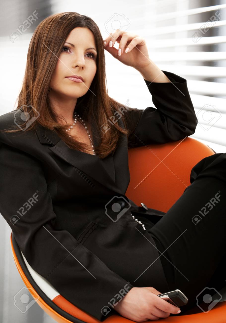 pensive businesswoman with cell phone in office Stock Photo - 18493655