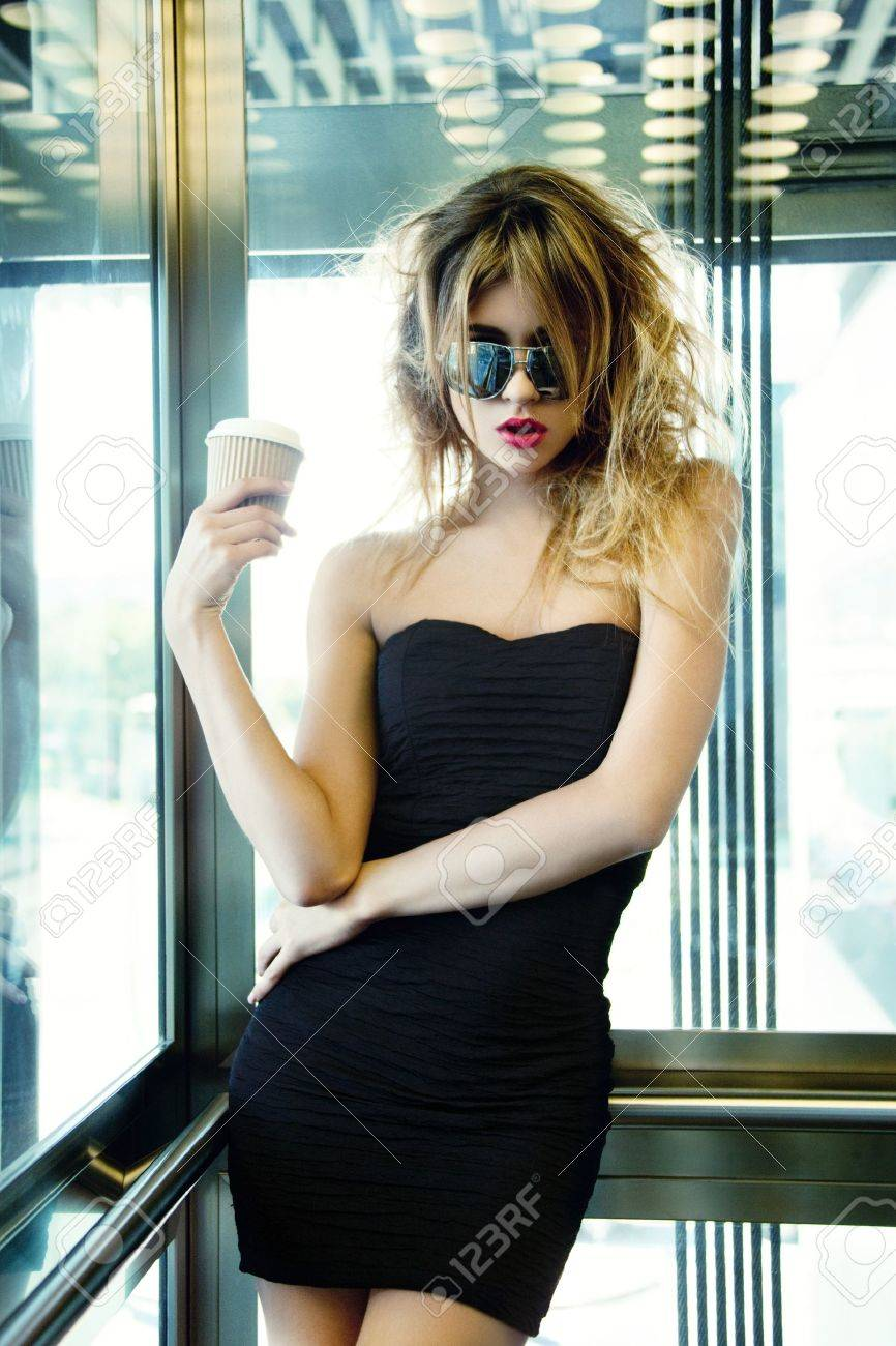 picture of girl posing in elevator with cup of coffee - 18655071