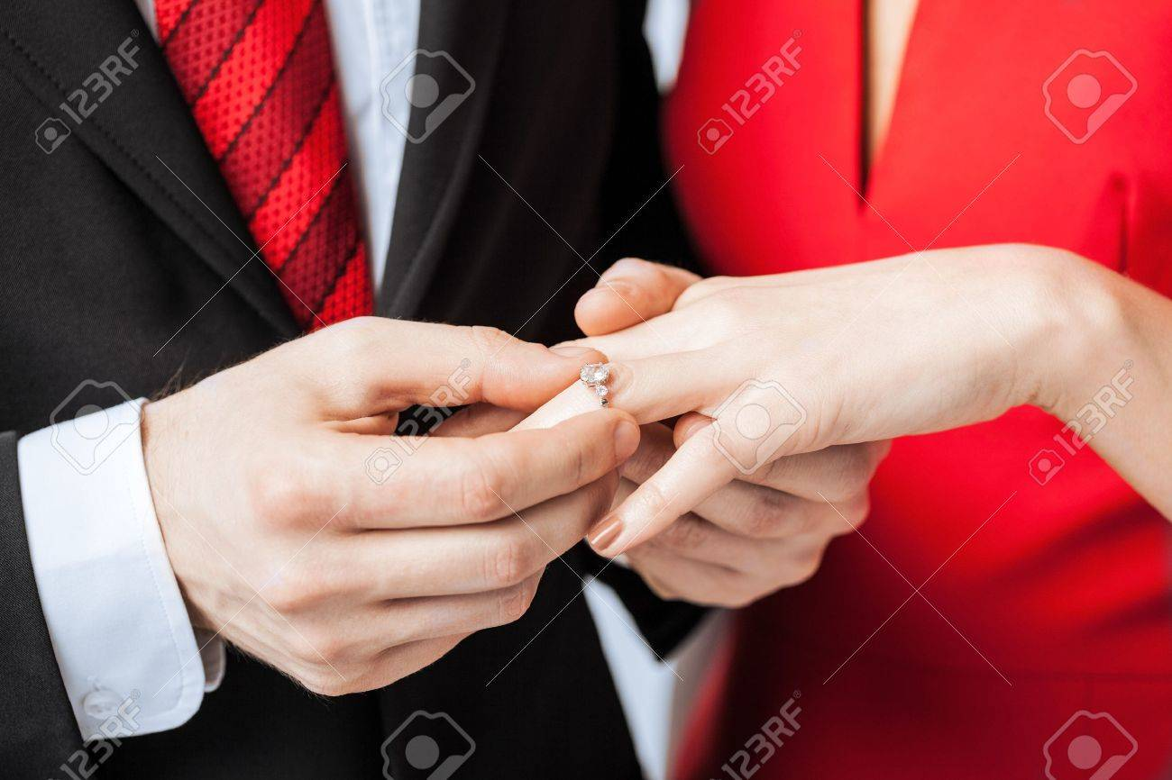 Picture of man putting wedding ring on woman hand stock photo picture of man putting wedding ring on woman hand stock photo 20112384 junglespirit Images