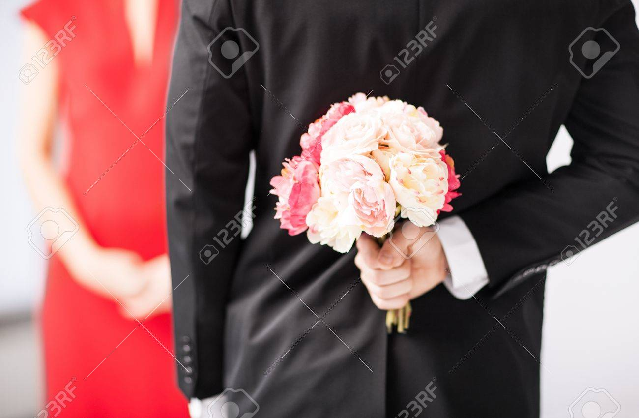 man hiding bouquet of flowers behind his back Stock Photo - 20112355