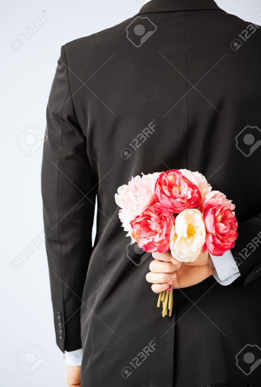 Man Hiding Bouquet Of Flowers Behind His Back Stock Photo Picture