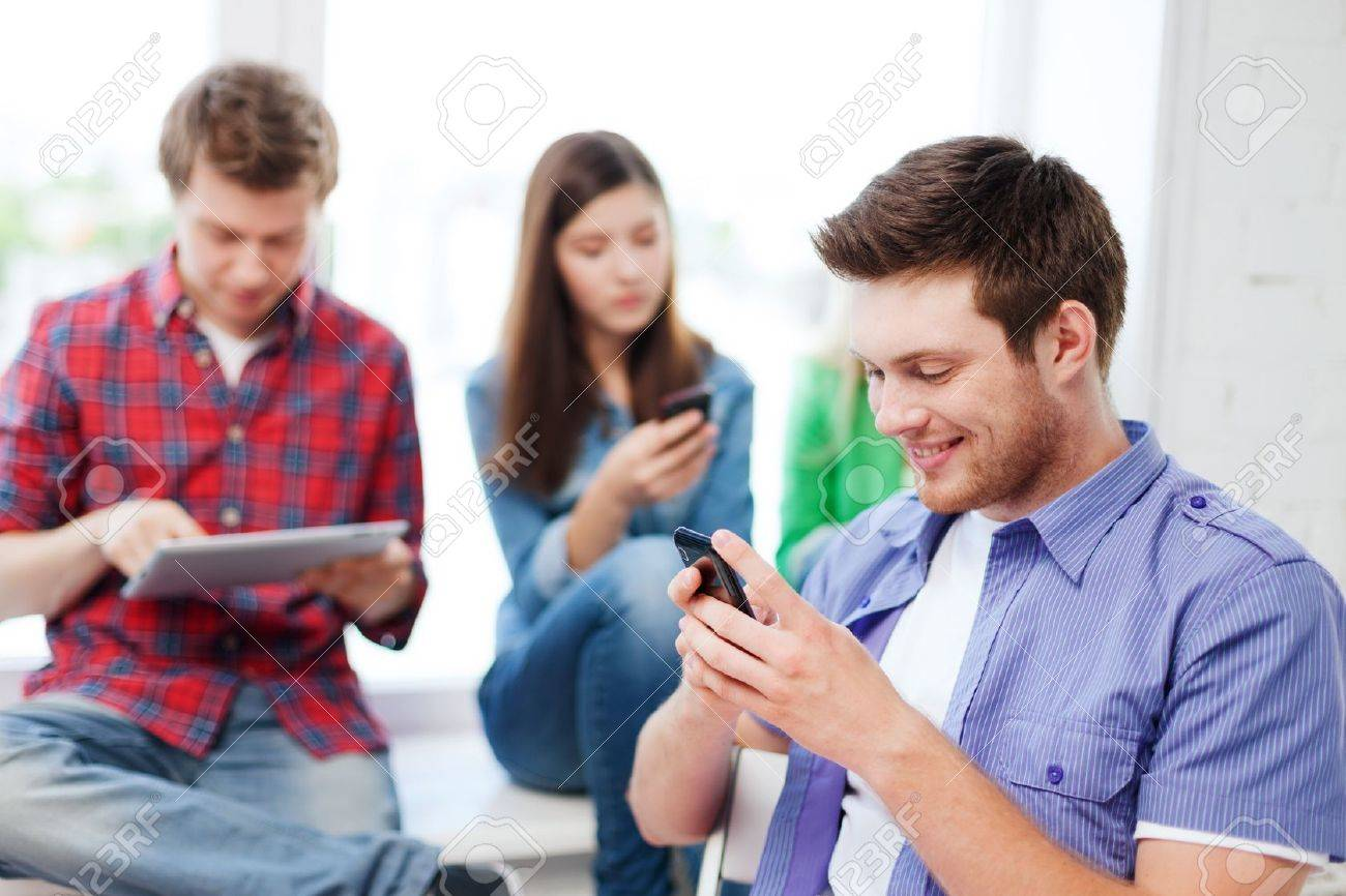 education concept - student looking into phone and writing at school Stock Photo - 20772536