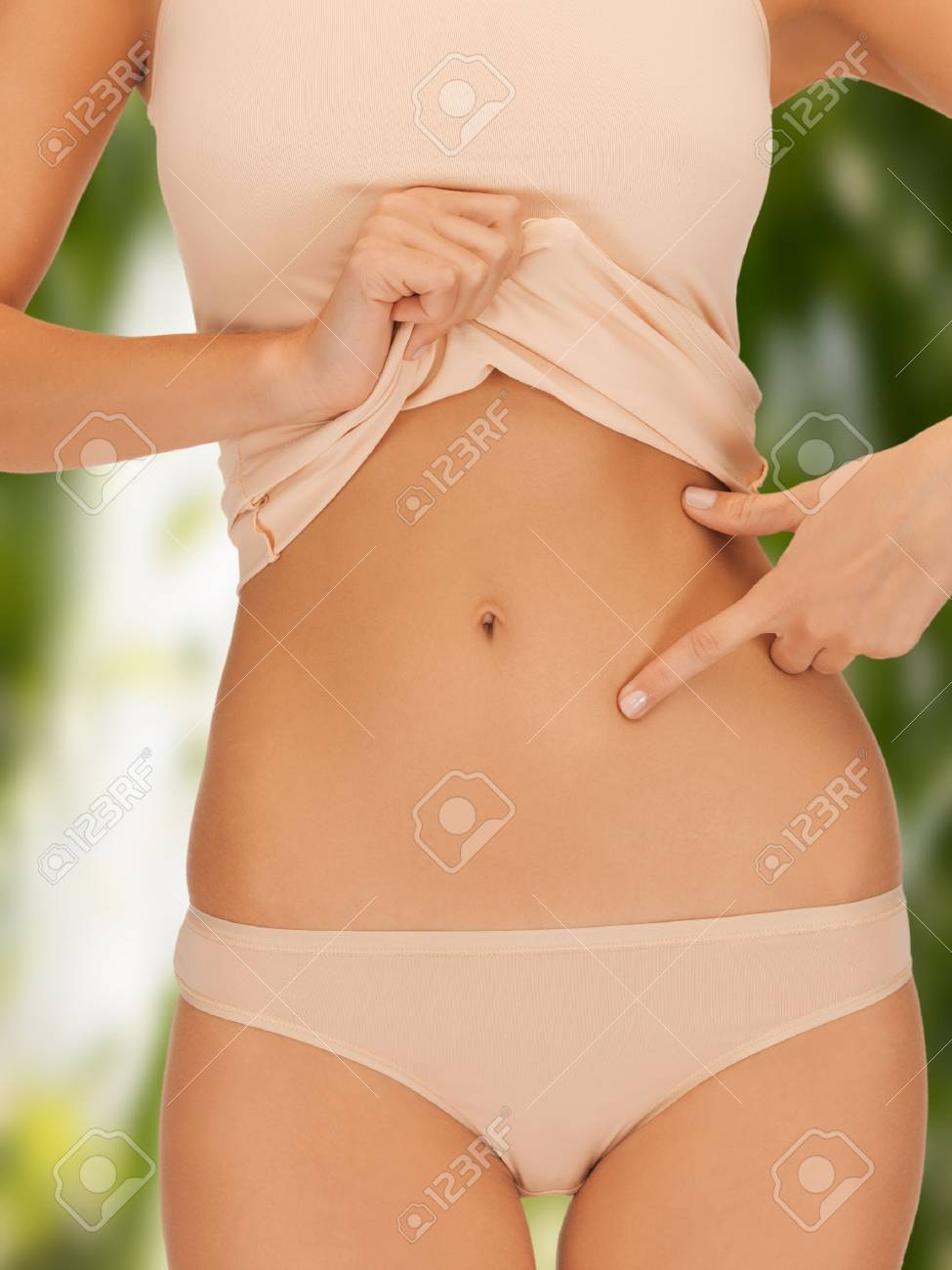 diet, slimming, health, beauty, eco, bio, pregnancy concept - woman pointing at her abs over green Stock Photo - 22380233