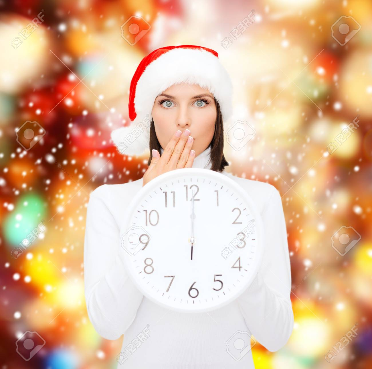 christmas, x-mas, winter, happiness concept - smiling woman in santa helper hat with clock showing 12 Stock Photo - 23317688