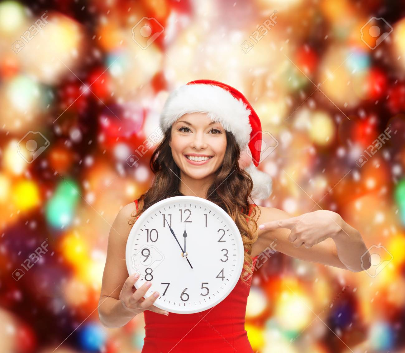 christmas, x-mas, winter, happiness concept - smiling woman in santa helper hat with clock showing 12 Stock Photo - 23450966