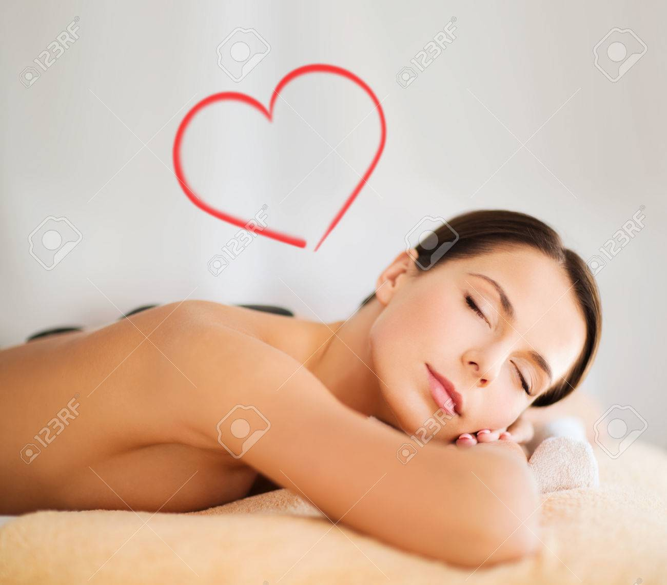 health and beauty, resort and relaxation concept - beautiful woman with closed eyes in spa salon with hot stones Stock Photo - 24371223