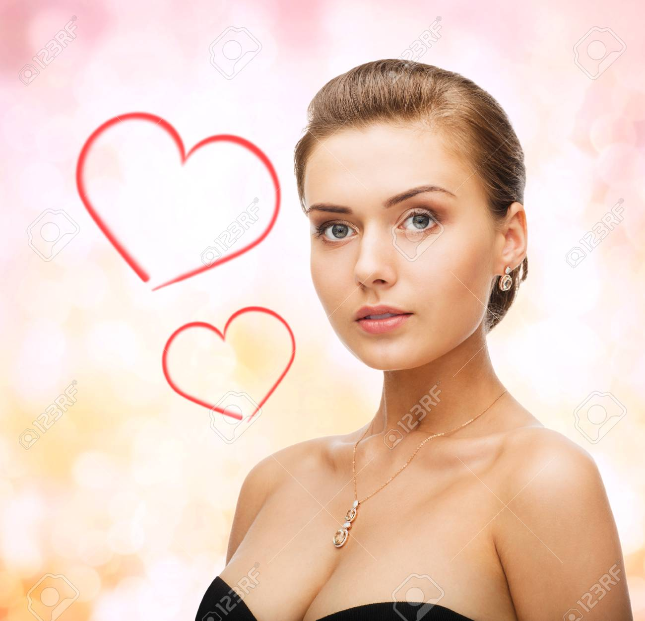beauty and jewelry concept - woman wearing shiny diamond earrings and pendant Stock Photo - 24371230