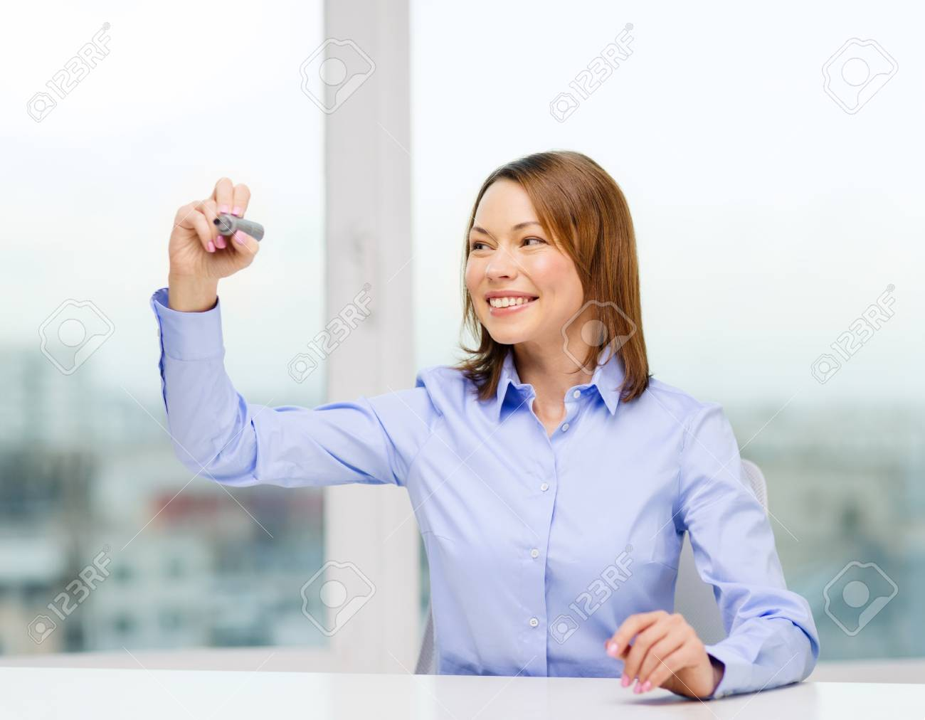 office, business, technology concept - businesswoman writing something in the air with marker Stock Photo - 25850896