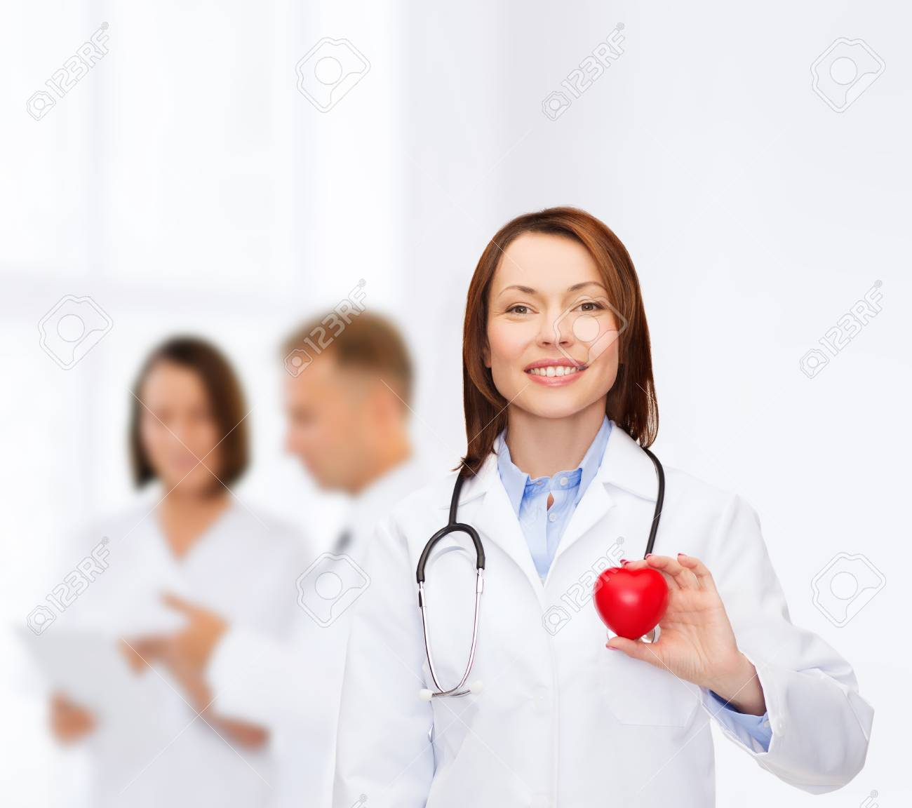 healthcare and medicine concept - smiling female doctor with heart and stethoscope Stock Photo - 26175586