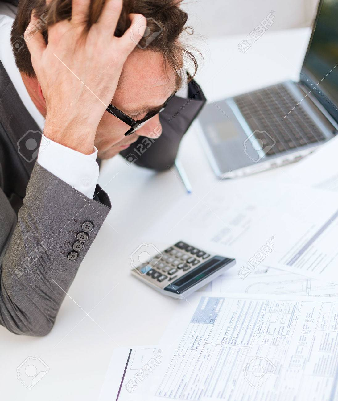 tax business and stress concept stressed businessman stock photo tax business and stress concept stressed businessman papres laptop and calculator
