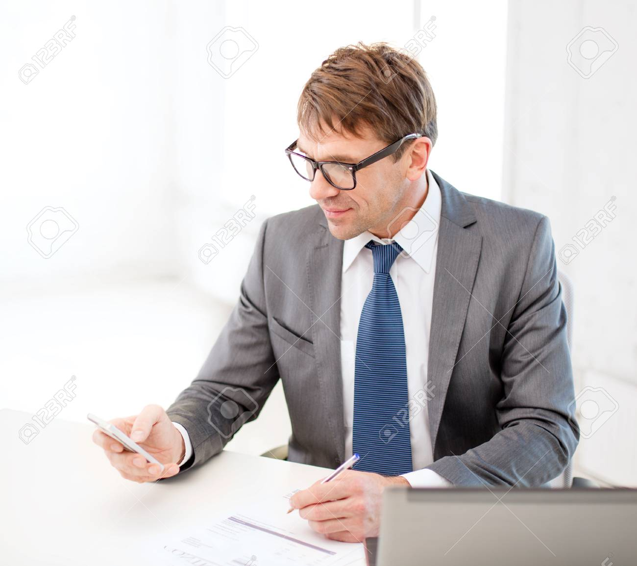 technology, business, internet and office concept - handsome businessman working with laptop computer and smartphone Stock Photo - 26175554