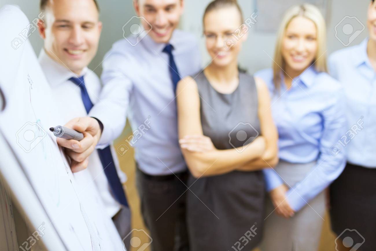 business and office concept - smiling business team with charts on flip board having discussion Stock Photo - 26175567