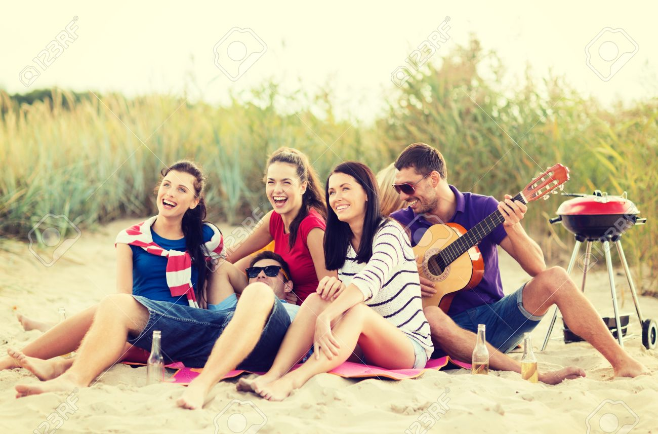 summer, holidays, vacation, music, happy people concept - group of friends with guitar having fun on the beach - 27906767