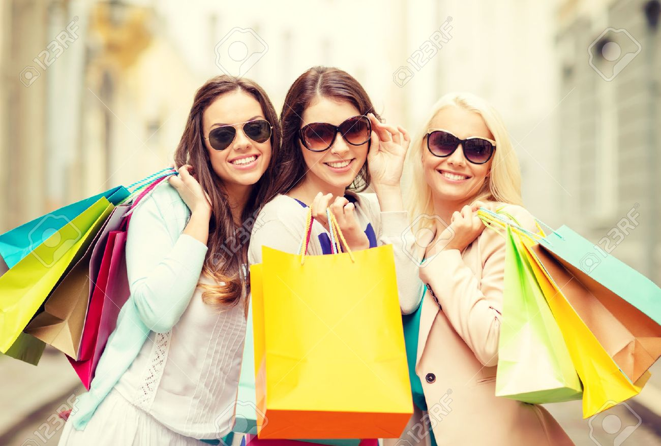 shopping, sale, happy people and tourism concept - three beautiful girls in sunglasses with shopping bags in ctiy - 28258749