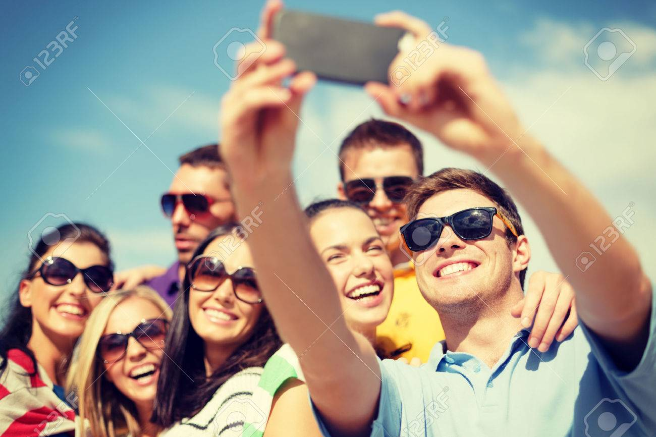 summer, holidays, vacation and happiness concept - group of friends taking picture with smartphone Stock Photo - 28508058