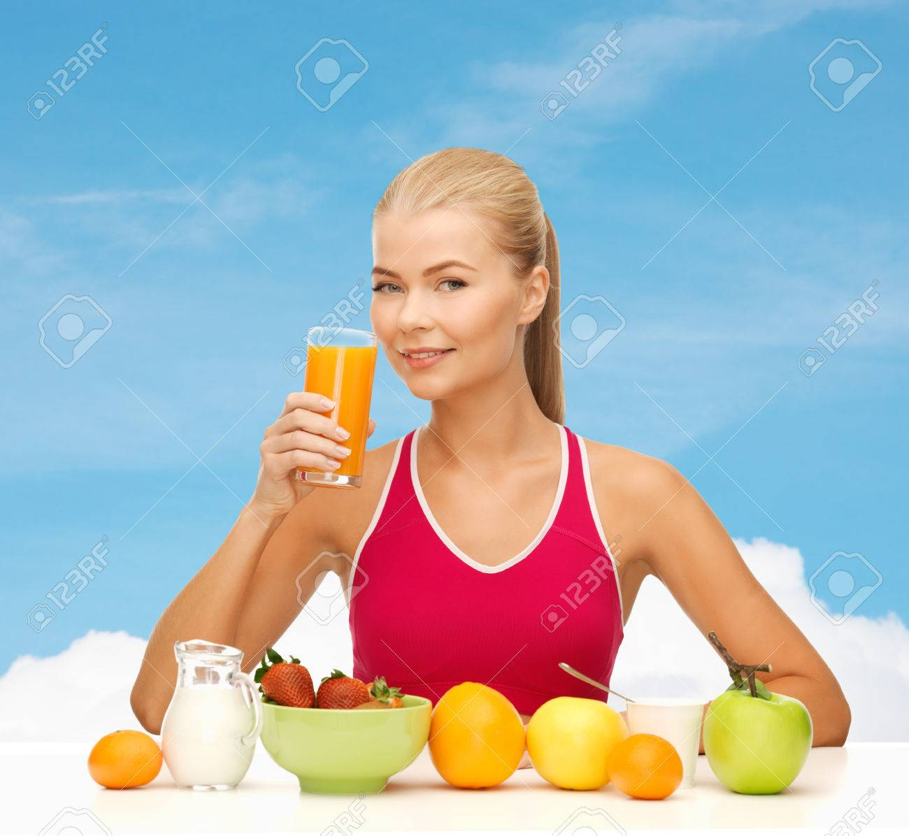 fitness, diet and healthcare concept - smiling young woman with healthy breakfast and drinking orange juice Stock Photo - 29246449