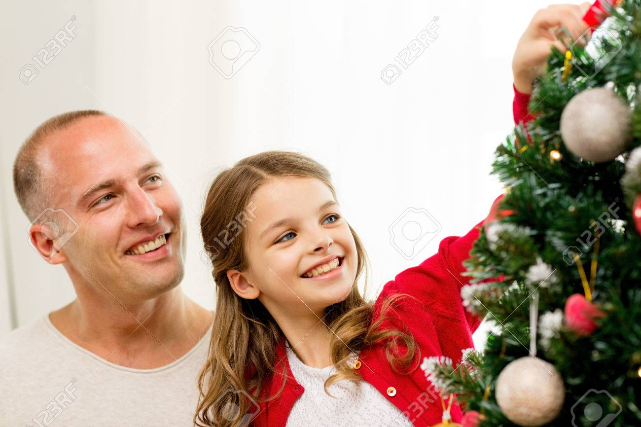 family holidays generation and people concept smiling girl with father decorating christmas tree - People Decorating A Christmas Tree