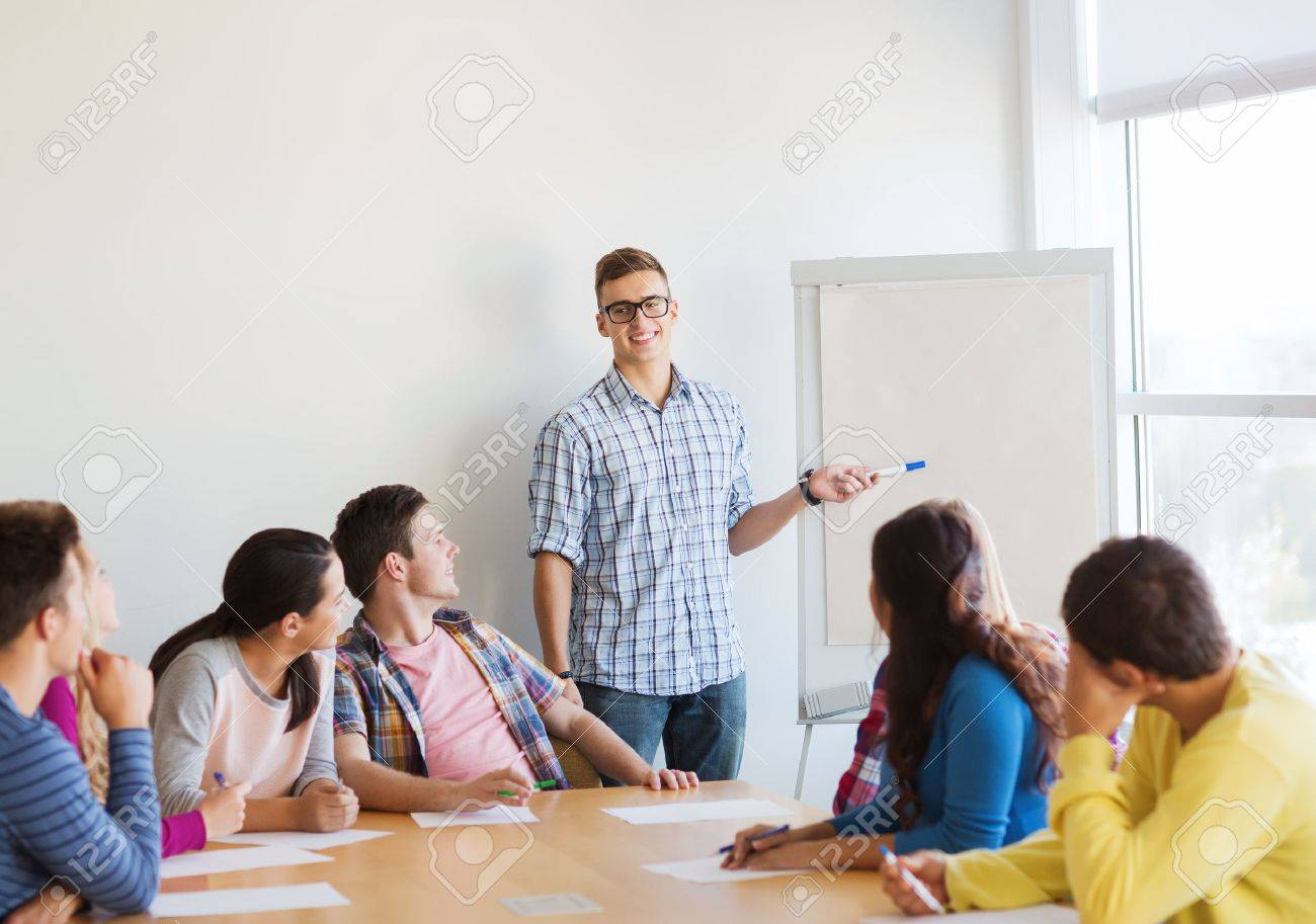 education, teamwork and people concept - smiling students with white board sitting an table indoors - 32578298
