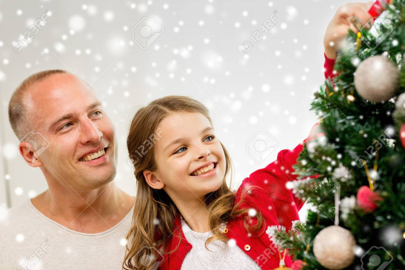 People Decorating A Christmas Tree smiling girl with father decorating christmas tree at home stock