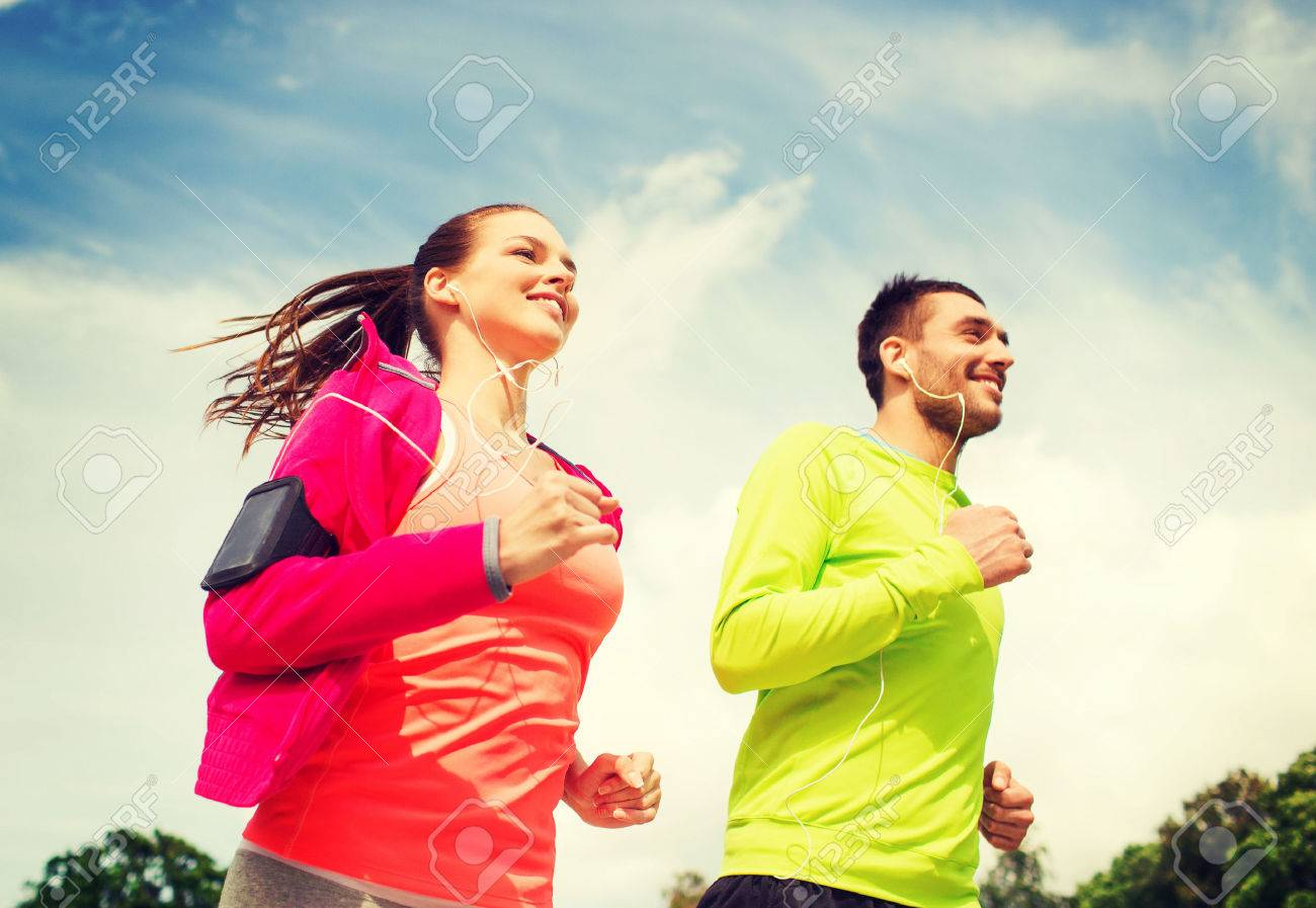 fitness, sport, friendship and lifestyle concept - smiling couple with earphones running outdoors - 34710008