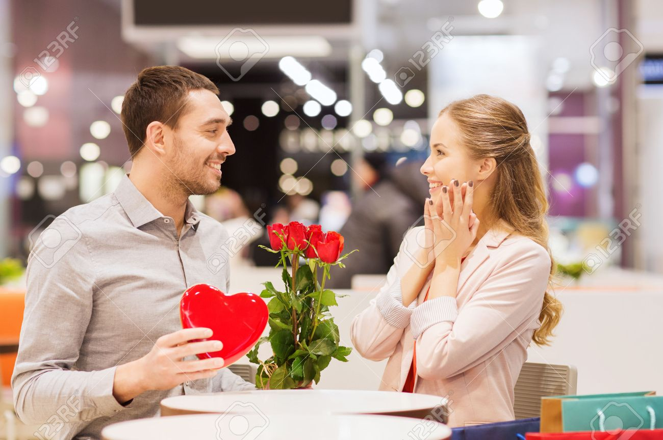 love, romance, valentines day, couple and people concept - happy young man with red flowers giving present to smiling woman at cafe in mall Stock Photo - 34812144