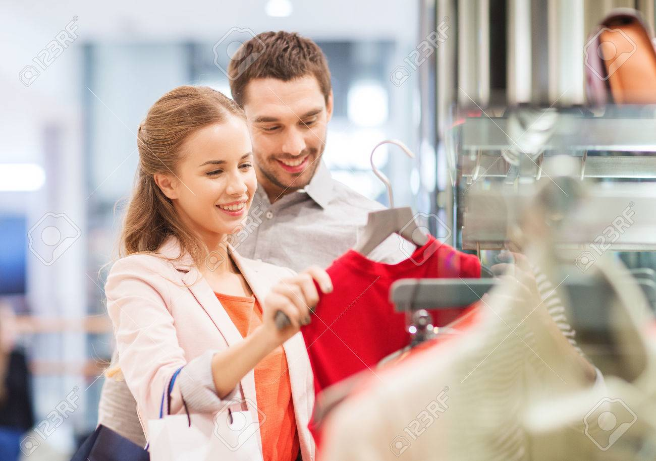 sale, consumerism and people concept - happy young couple with shopping bags choosing dress in mall - 34812383