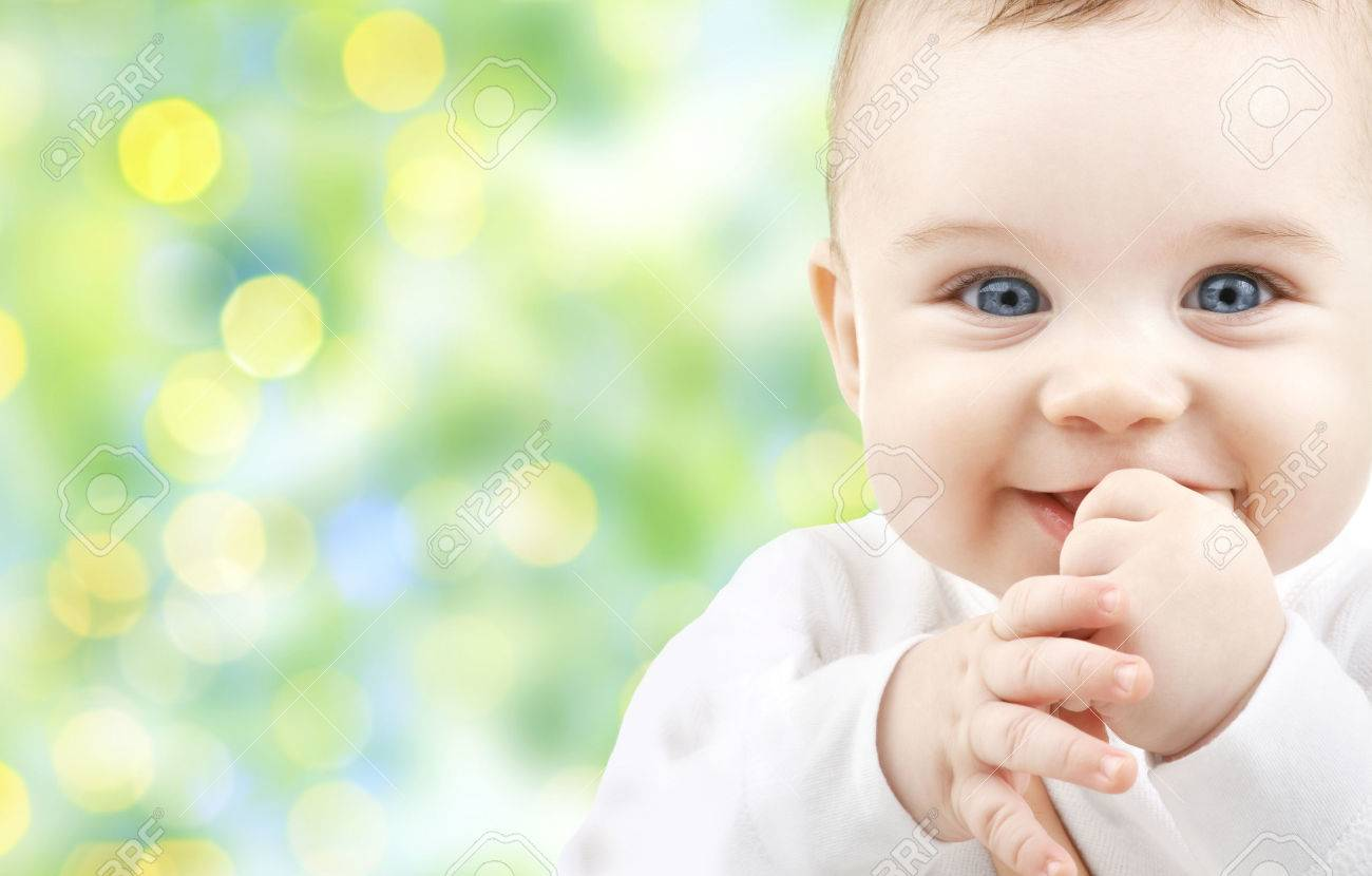 children, people, infancy and age concept - beautiful happy baby over green lights background Stock Photo - 35519360
