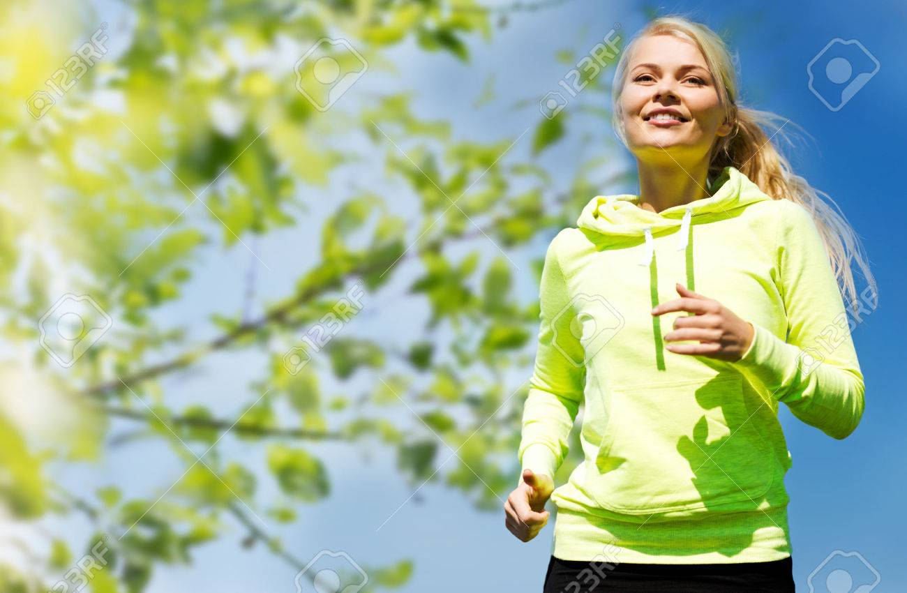 fitness, people and healthy lifestyle concept - happy young female runner jogging outdoors - 36669183