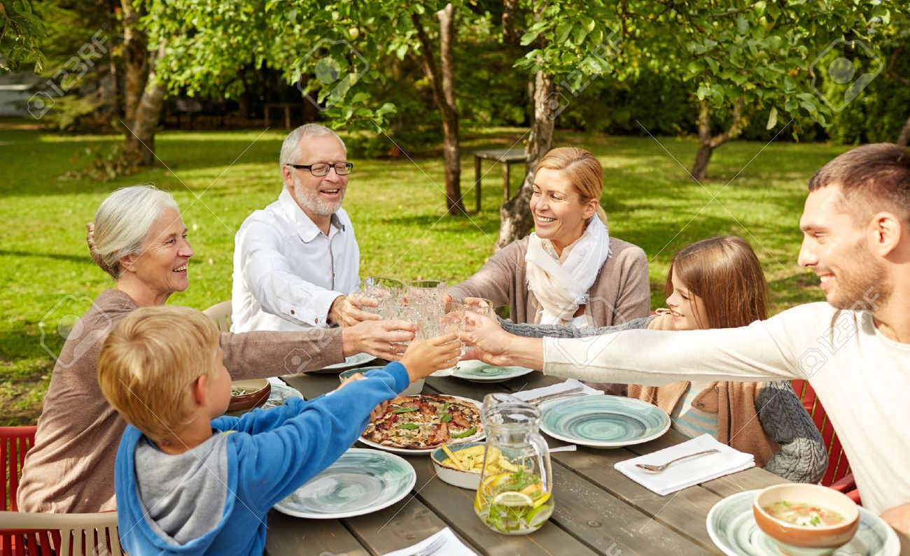 family, generation, home, holidays and people concept - happy family having dinner and clinking glasses in summer garden - 37107069