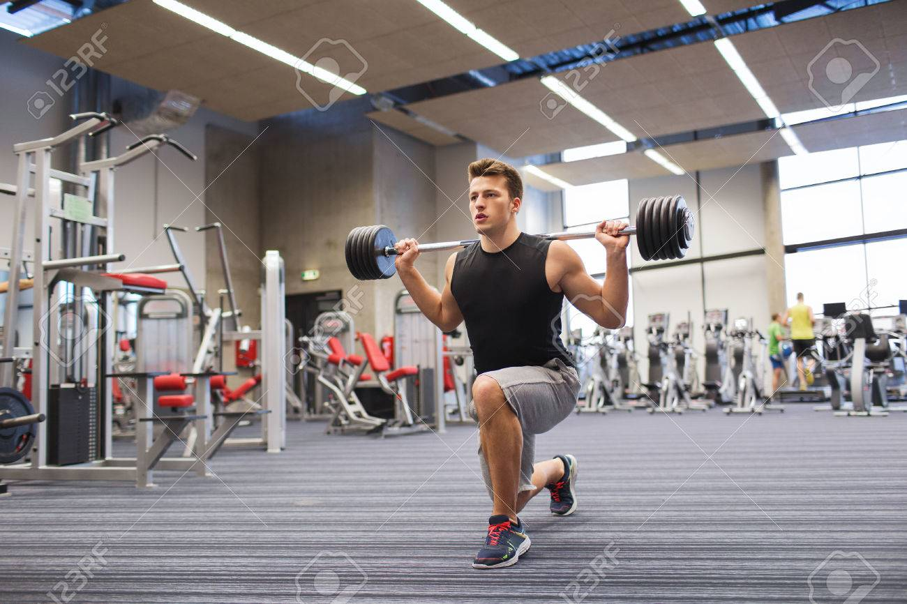 sport, bodybuilding, lifestyle and people concept - young man with barbell flexing muscles and making shoulder press lunge in gym - 37674314