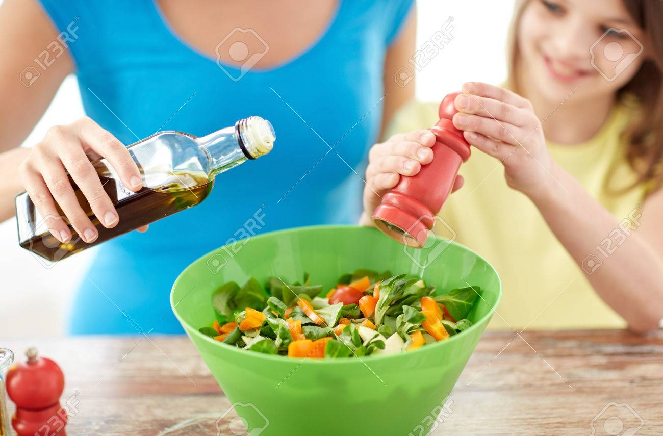 food, healthy eating, family and people concept - close up of happy girl and mother cooking salad for dinner and adding spices in kitchen - 37682533